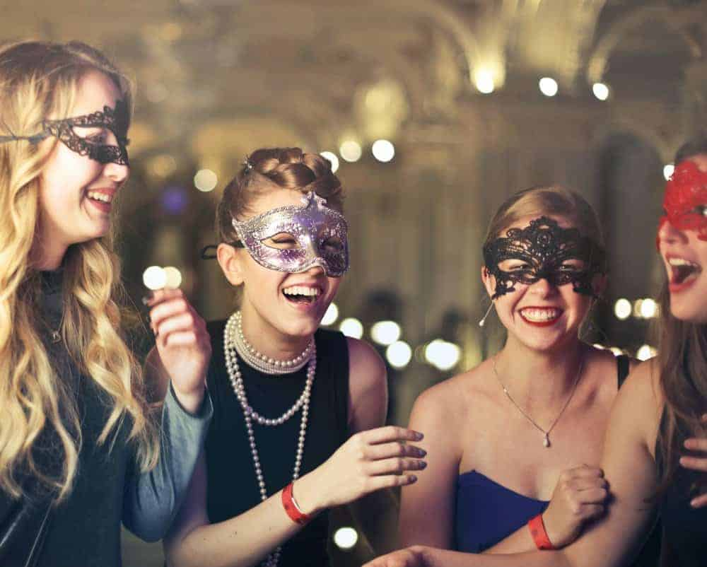 four women laughing and smiliing while wearing masquerade masks at a costume party