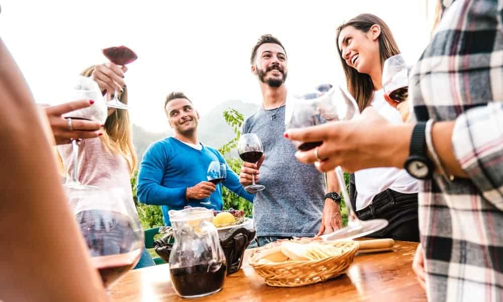 group of friends drinking wine around an outdoor table celebrating and laughing