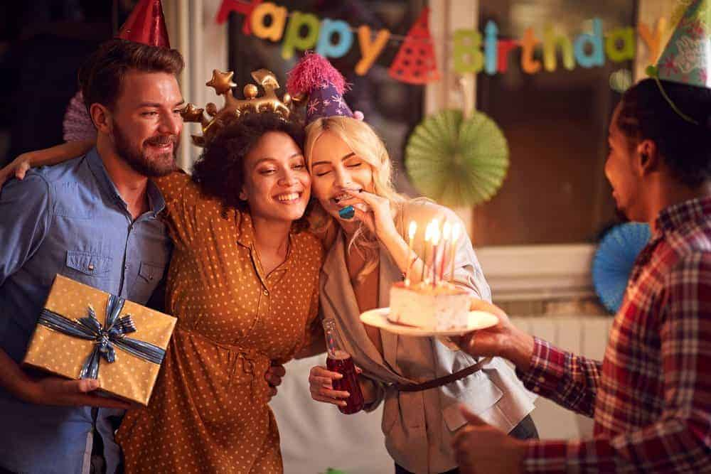 Adults celebrating a friend's birthday party with party decoration, a gift and cake with lit candles