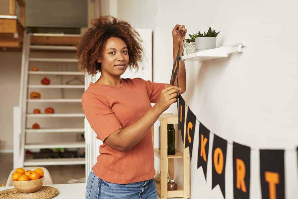 Attractive young African American woman decorating room with garland for Halloween party