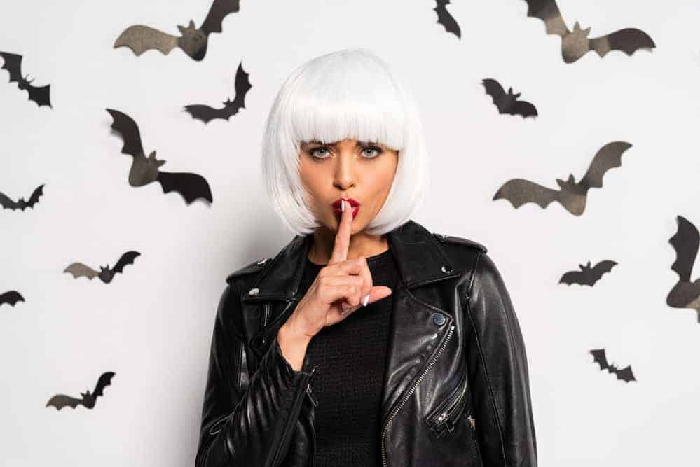 woman in white wig holding a finger to symbolize quiet with paper bats hung all around