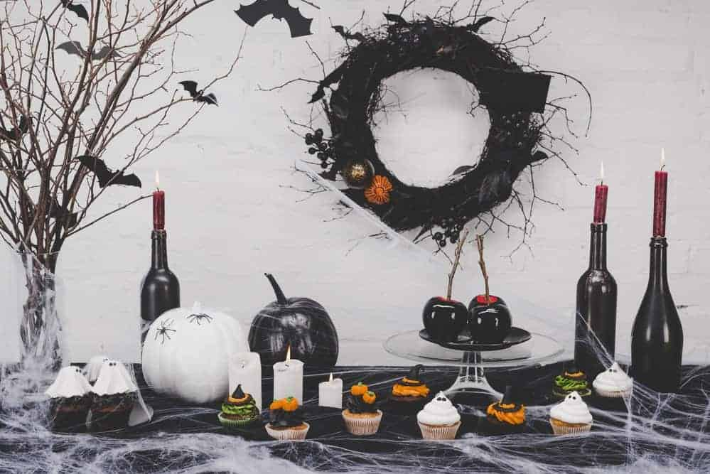 spooky office halloween decorations with modern flair including black and white pumpkins, red candles in wine bottles, and bats on branches with black wreath