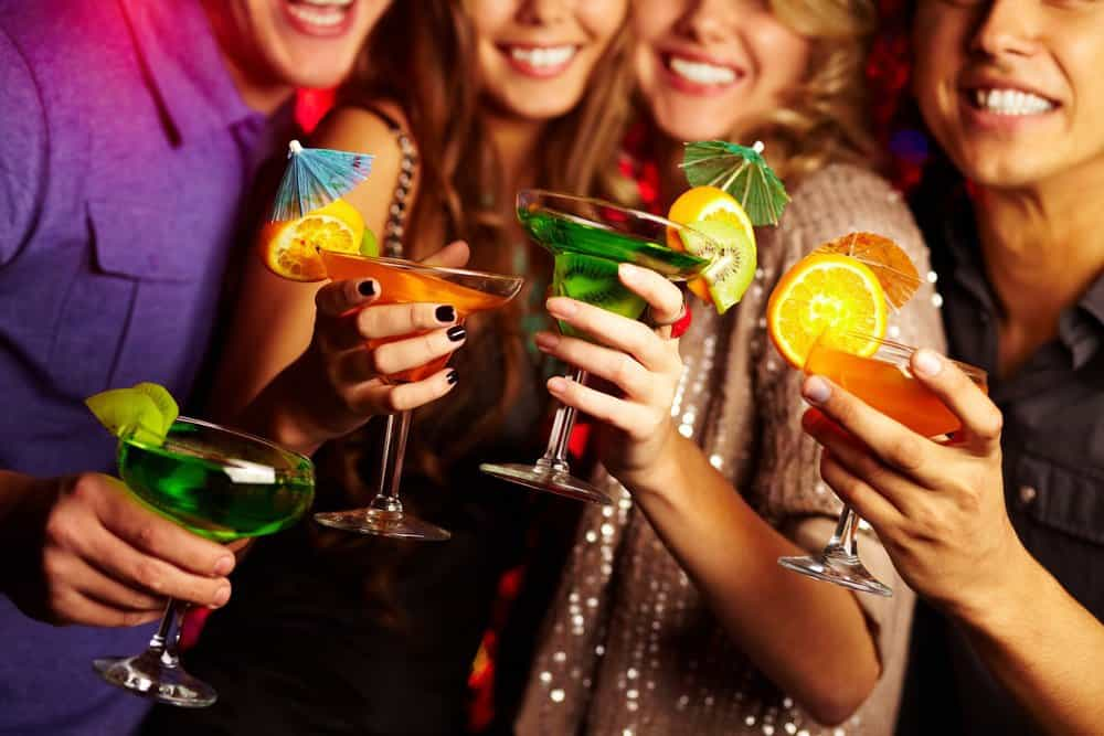 group of friends holding fun and colorful mixed drinks with fruit and umbrella picks in a party setting