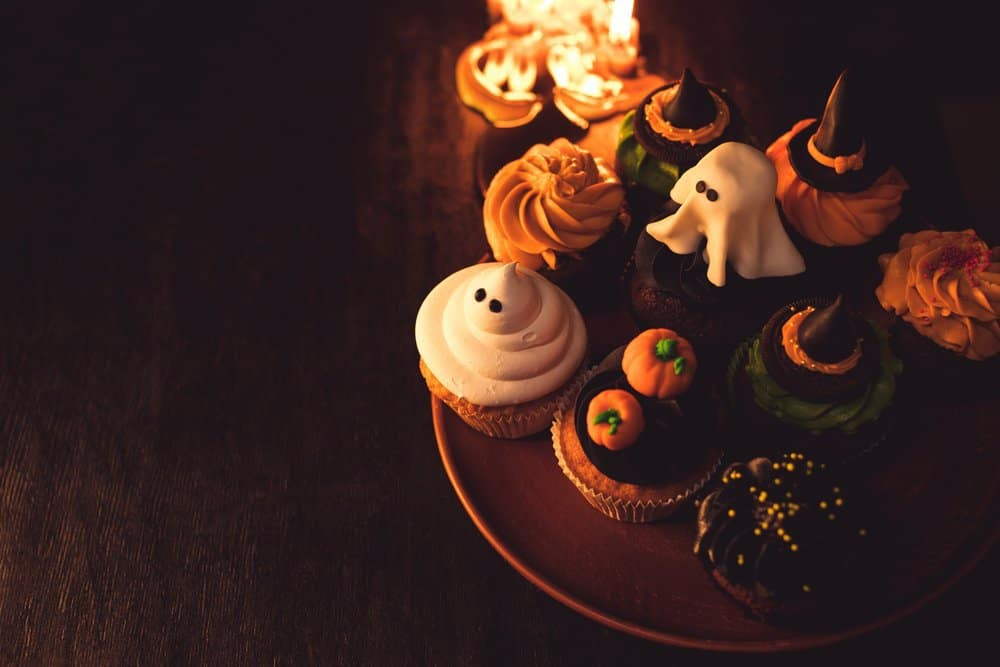 decorated halloween cupcakes with orange, black and white frosting and halloween themed candy