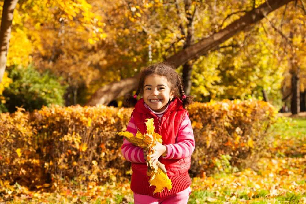 smiling girl playing outside in fall leaves