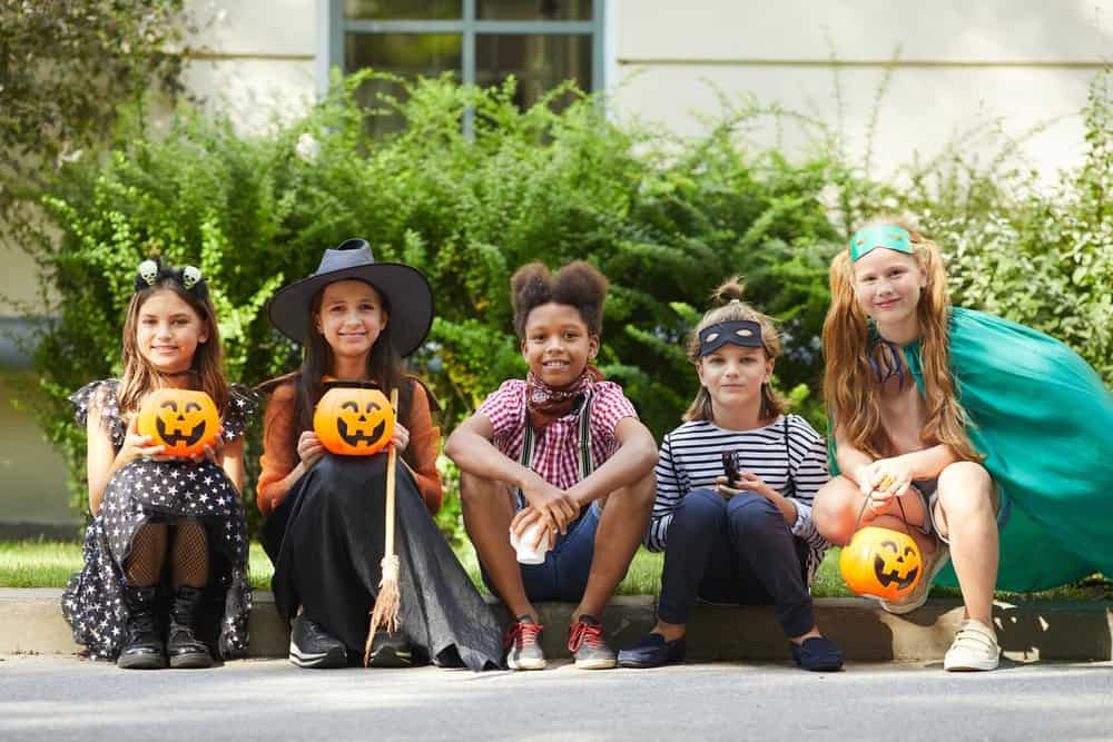 group of preteens at halloween party for kids sitting on a sidewalk stoop and smiling for the camera