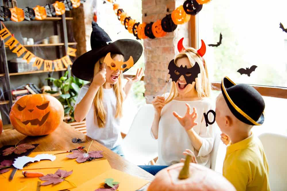 kids and mom creating halloween photo booth props for a fun halloween party for kids with lots of decorations around