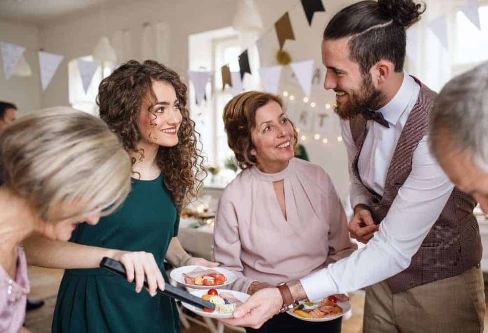 party host serving food to party guests at and indoor party