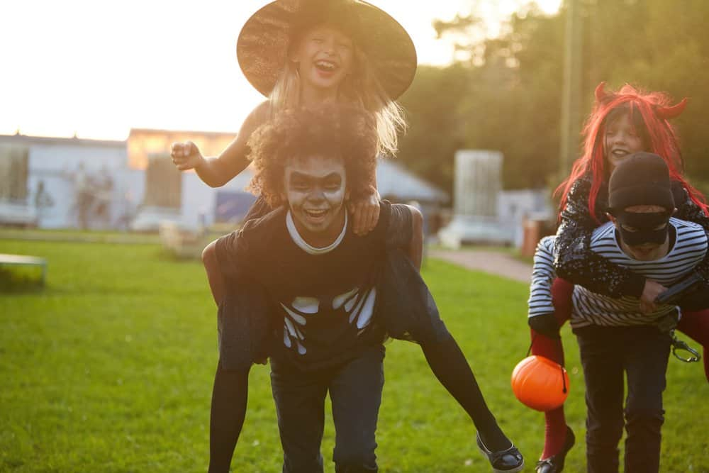 preteen kids wearing halloween costumes and playing an kids halloween party game by giving piggy back rides to friends in a relay